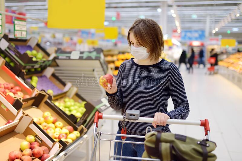 Young woman wearing disposable medical mask shopping in supermarket during coronavirus pneumonia outbreak. Protection and prevent measures while epidemic time stock photography