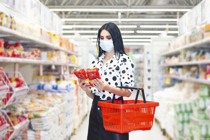 Young woman wearing disposable medical mask shopping in supermarket stock photo