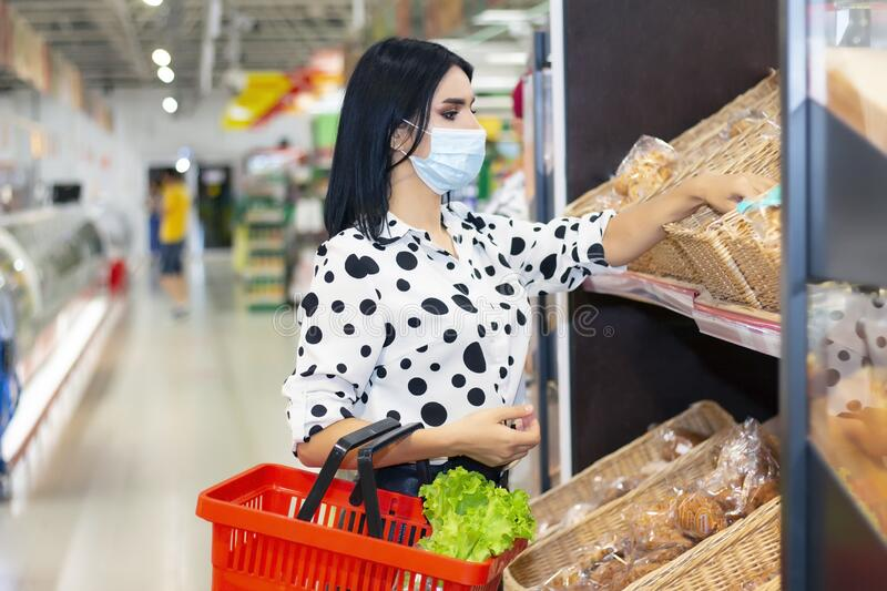 Young woman wearing disposable medical mask shopping in supermarket royalty free stock photography