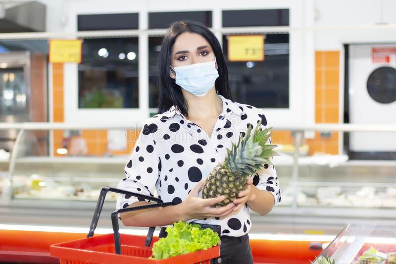 Young woman wearing disposable medical mask shopping in supermarket royalty free stock image