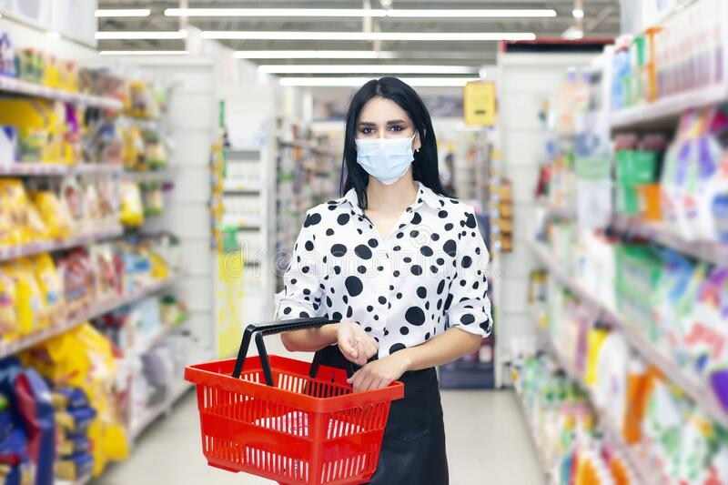 Young woman wearing disposable medical mask shopping in supermarket royalty free stock images