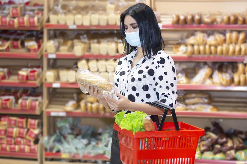 Young woman wearing disposable medical mask shopping in supermarket stock image