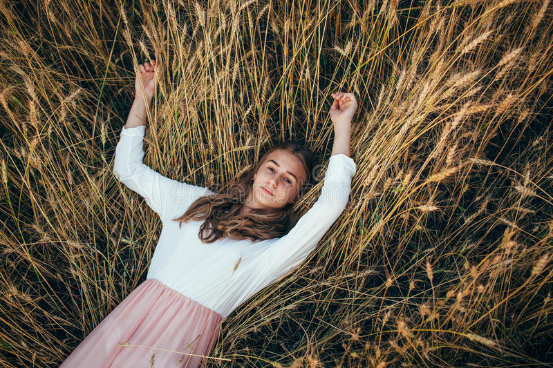 Young woman wearing dress lying in field with wheat stock images