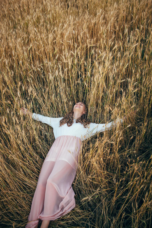 Young woman wearing dress lying in field with wheat stock photo