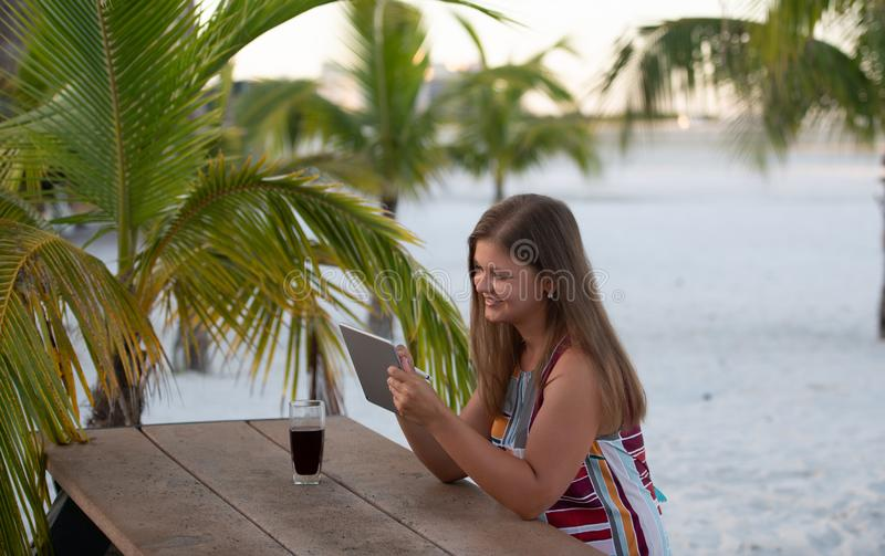 Young woman with tablet on the beach. Young woman wearing dress using tablet on the beach in the morning on the background of palm trees in Florida with glass of royalty free stock photos
