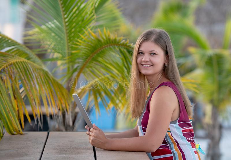 Young woman with tablet on the beach. Young woman wearing dress using tablet on the beach in the morning on the background of palm trees in Florida royalty free stock photos