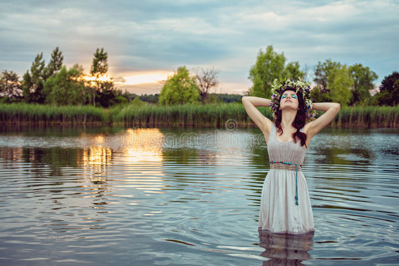 Young woman wearing flower wreath and staying in the water. Young beautiful drowned woman in gey dress stying in the water at the lake stock photography