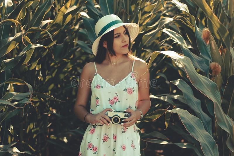 Young woman wearing a flowery white dress taking photos with retro photo camera stock images