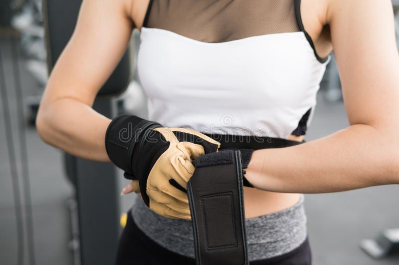 young woman wearing gloves in fitness center. female athlete prepare for training in gym. sporty girl ready for working out in he royalty free stock image