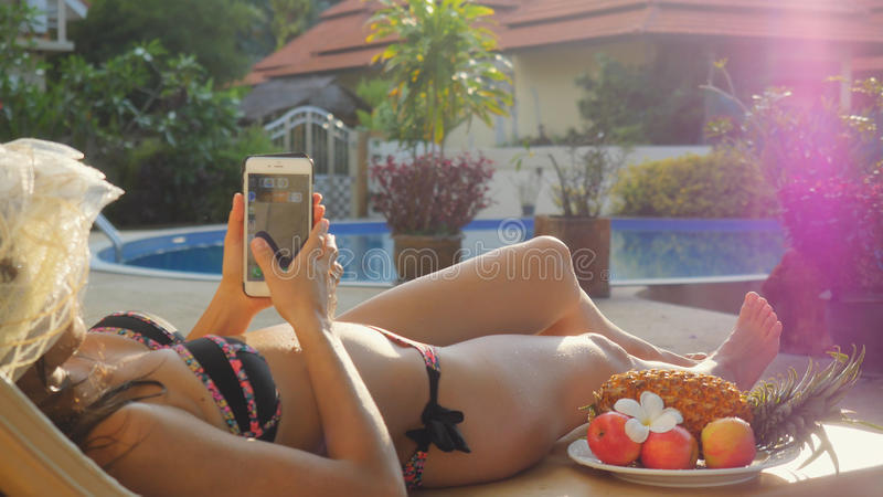 Young woman wearing hat lies on a sunbed uses smart phone next to the swimming pool on summer holidays with beautiful stock photography