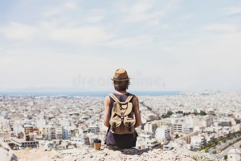 Young woman wearing hat looking at a big city. Traveler girl enjoying vacation. Summer holidays, vacations, travel, concept stock image