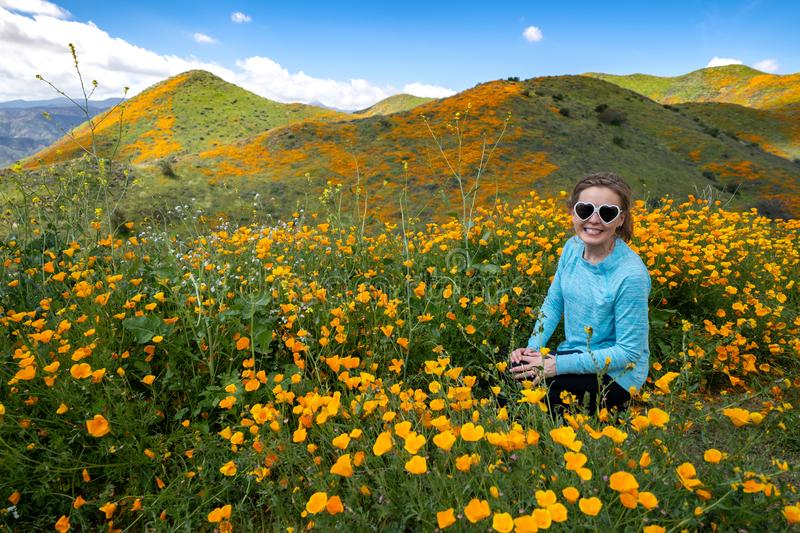 Young woman wearing heart sunglasses and casual clothing poses in poppy field royalty free stock photos
