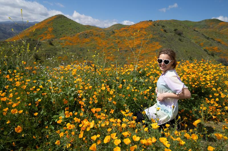 Young woman wearing heart sunglasses and casual clothing poses in poppy field.  royalty free stock photography