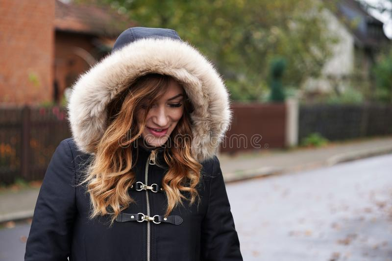 Young woman wearing hooded winter coat playing coy. On suburban street in Germany royalty free stock photo