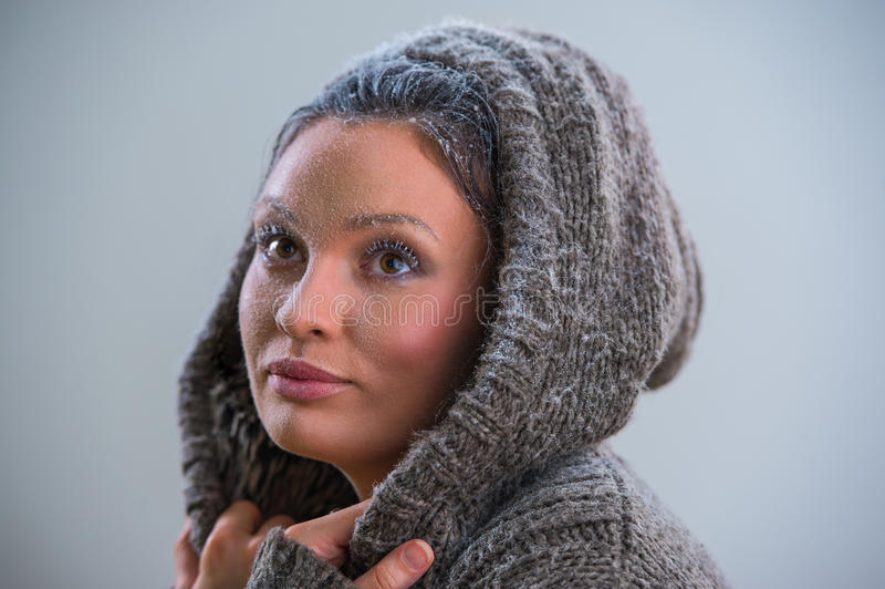 Young woman wearing hoodie in frost. Young woman wearing hoodie warming after cooling in snow. Frost makeup stock images