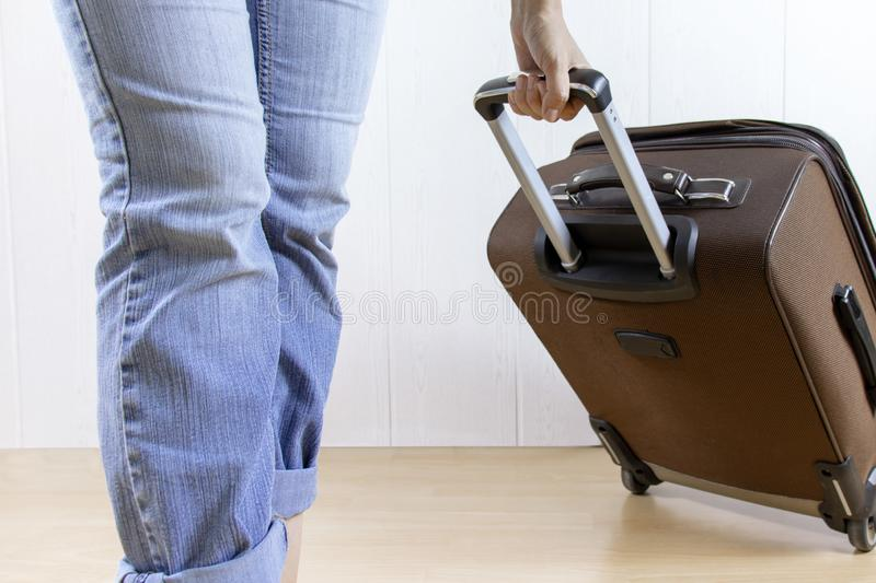 Young woman wearing jeans carry a luggage bag. Travel and relocation concept. Young woman wearing jeans carry a luggage bag. Travel and relocation concept stock photography