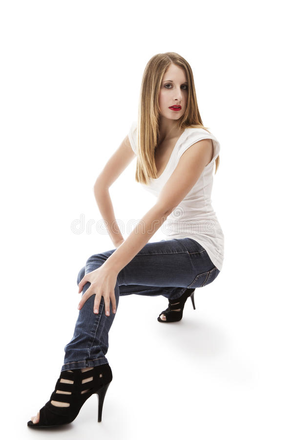 Young woman wearing jeans crouching. On white background royalty free stock photo