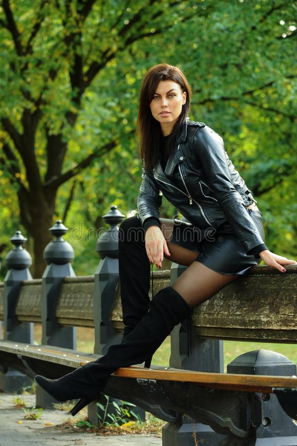 Young woman wearing leather jacket, mini skirt and over-knee boots posing at the autumn park. Attractive young woman wearing leather jacket, mini skirt and over stock image