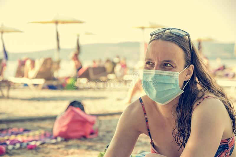 Young woman wearing medical mask sitting at the beach. New normal concept. Life after coronavirus pandemic, travel and vacations at sea with new rules theme royalty free stock image