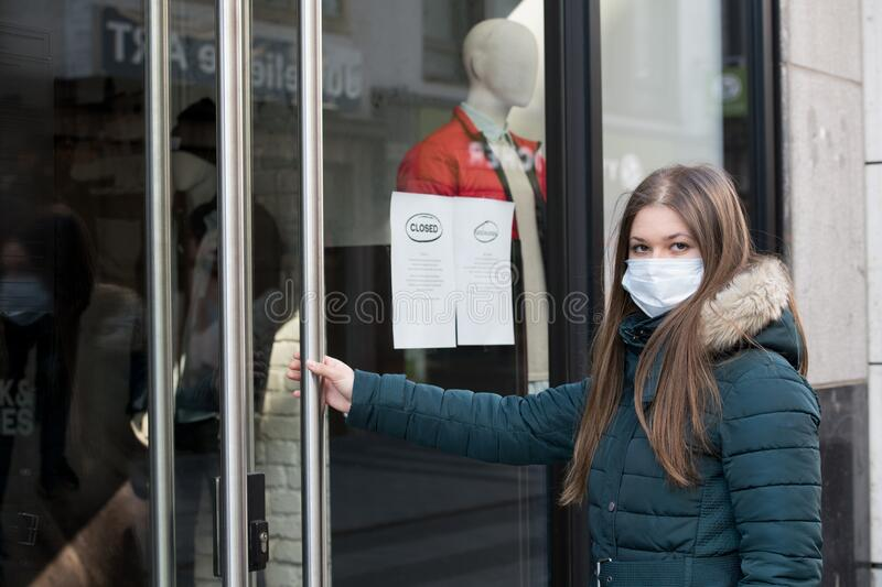 Young woman wearing medical protective mask in the front of clodes shop stock photos
