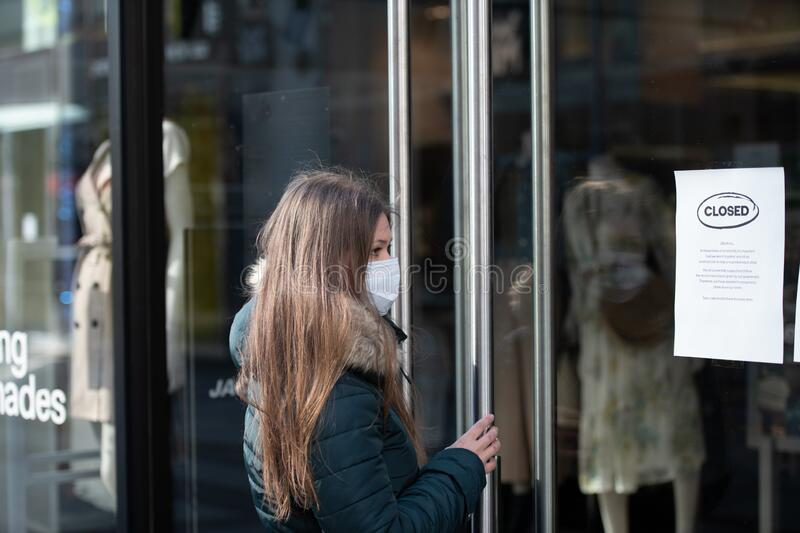 Young woman wearing medical protective mask in the front of clodes shop royalty free stock images