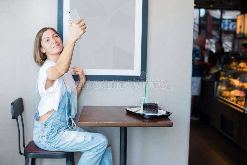 Young woman wearing overalls tshirt taking selfie. Young woman wearing overalls white tshirt taking selfie sitting table cafe eating coffee cake. using mobile royalty free stock images