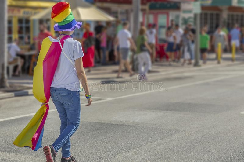 A young woman wearing a pride top hot and rainbow flag cape walk away stock image