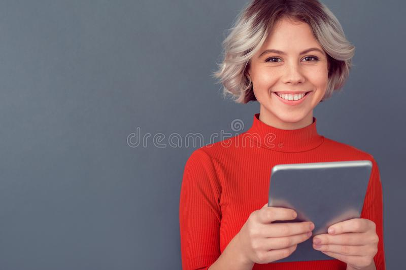 Young woman in a red blouse isolated on grey wall online shopping royalty free stock photography