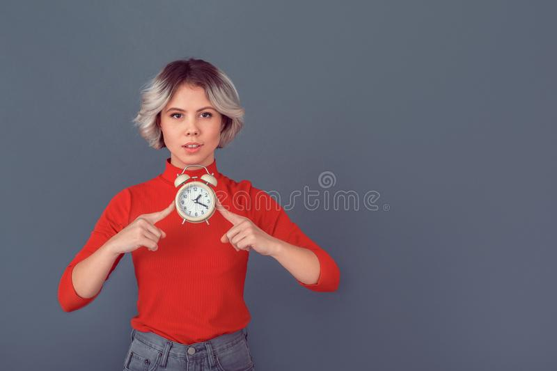 Young woman in a red blouse on grey wall time royalty free stock image