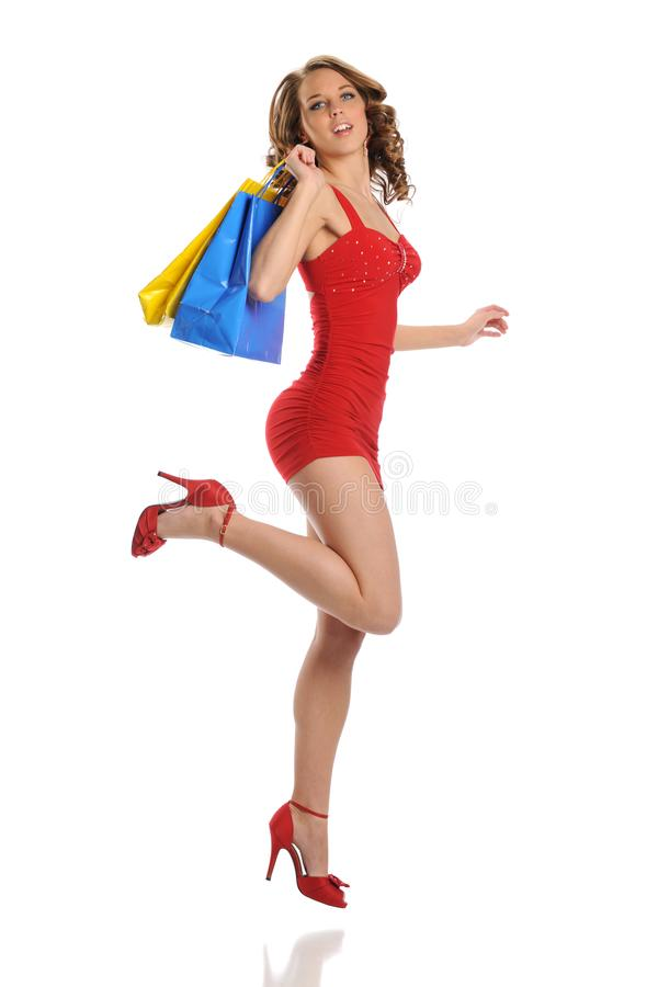 Young woman wearing red dress with shopping bags royalty free stock photo