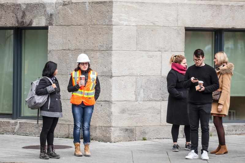 Young woman wearing safety PPE equipment, a helmet and an orange visibility vest discussing during her break stock photos