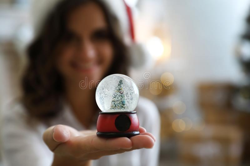 Young woman wearing Santa hat, focus on hand with Christmas snow globe stock photo