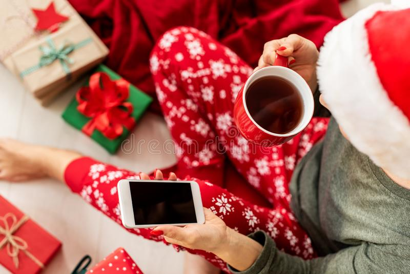 Young woman wearing santa hat and xmas pajamas sitting on the floor amongst wrapped christmas presents, shopping on her phone. stock image