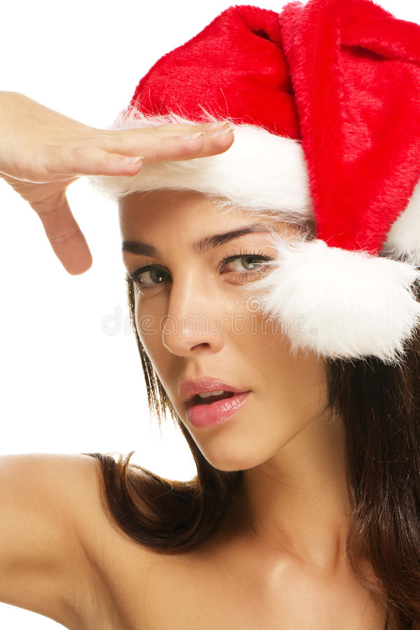 Young woman wearing santas hat shields her sight