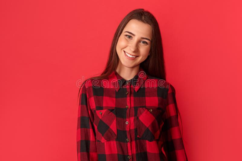 Freestyle. Young woman standing on red smiling cheerful to camera royalty free stock image