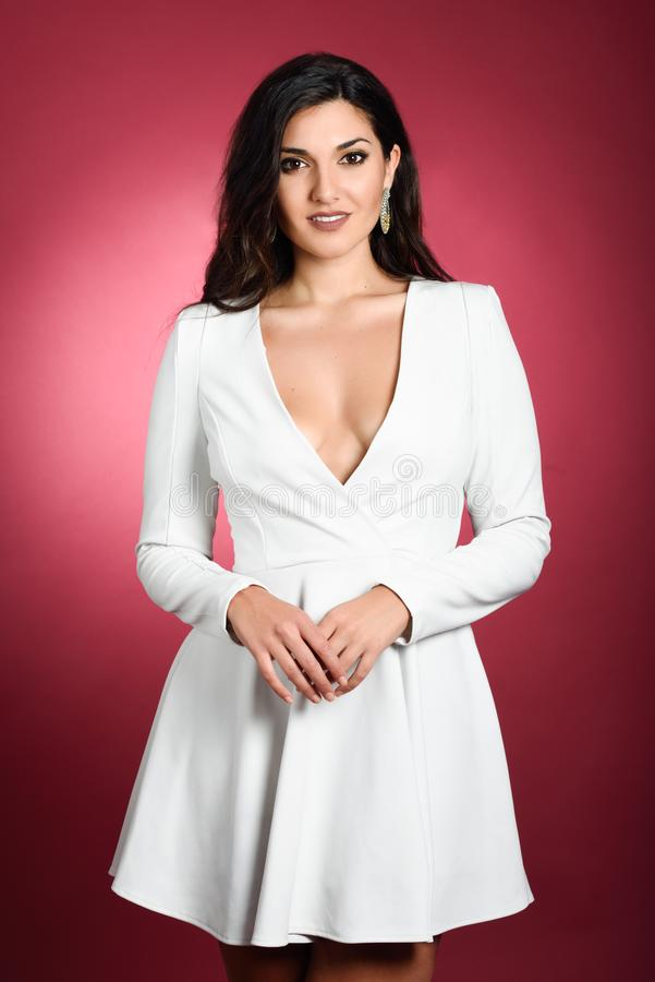 Young Woman Wearing Short White Dress On Red Background ...