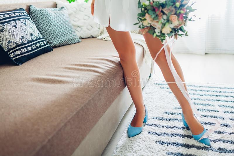 Young woman wearing silk dressing gown and blue shoes and holding bouquet at home. Morning of bride on wedding day stock photos