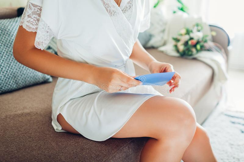 Young woman wearing silk dressing gown and opening envelope with vows at home. Morning of bride on wedding day. Young woman wearing silk dressing gown and stock image