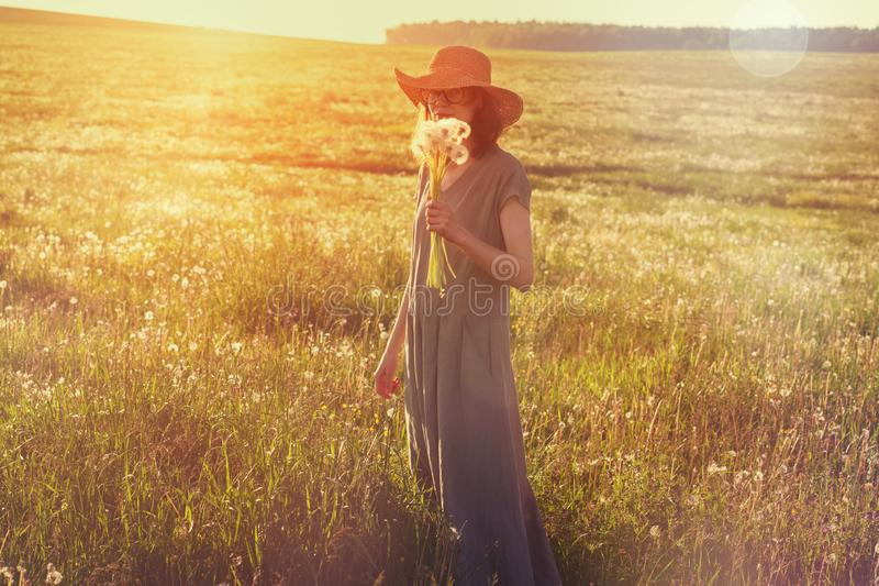 Woman wearing straw hat and long linen dress enjoying nature, holding bouquet of fresh beautiful dandelions, hot summer sunny day. Young woman wearing straw hat stock image