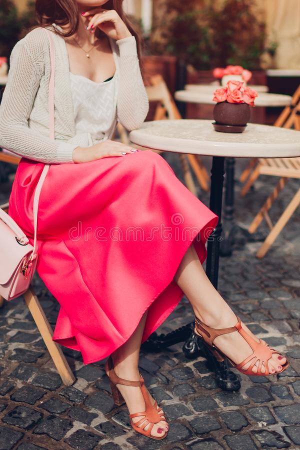 Young woman wearing stylish outfit with accessories in outdoor cafe. Close-up of female legs with shoes stock photo