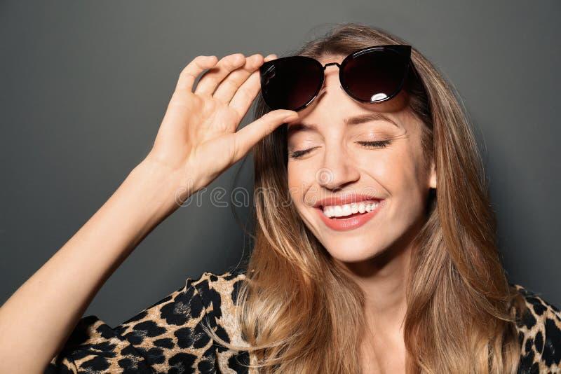 Young woman wearing stylish sunglasses on grey background royalty free stock image