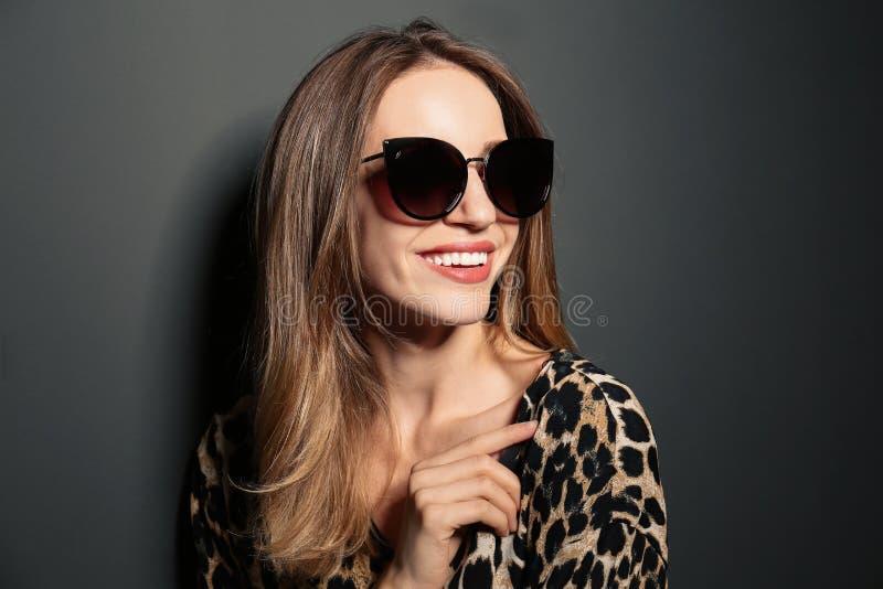 Young woman wearing stylish sunglasses on grey background stock image