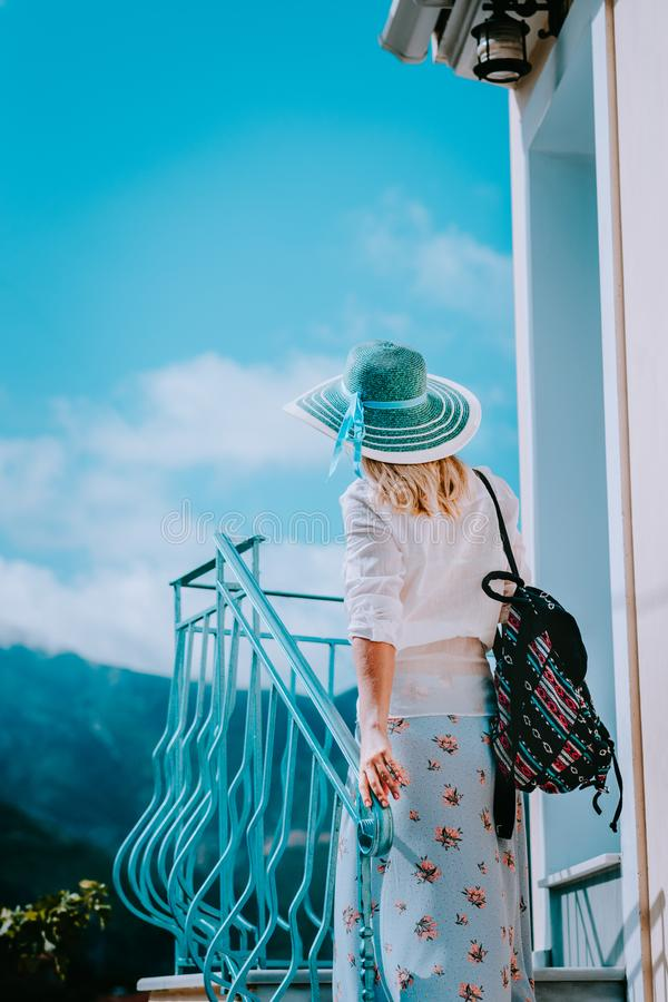 Young woman wearing summer clothes and straw hat going up stairs on sunny day. Vacation holidays in Europe stock photo