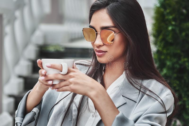 Young woman in sunglasses sitting at table in cafe with cup of c royalty free stock image