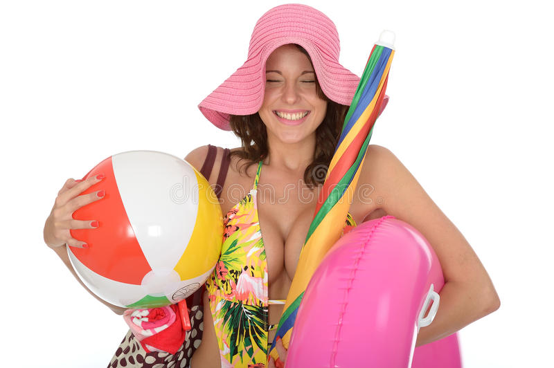 Young Woman Wearing a Swim Suit on Holiday Carrying a Beach Ball. A DSLR royalty free image, of excited and and very happy young woman smiling with eyes shut on royalty free stock images
