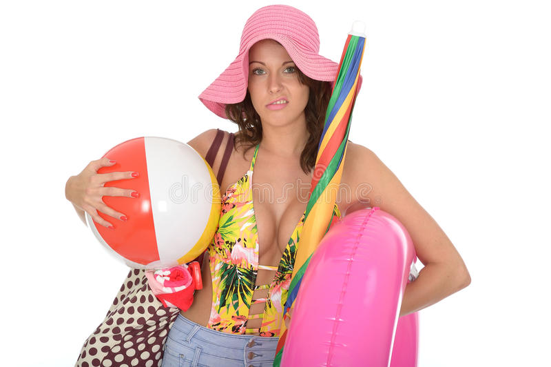 Young Woman Wearing a Swim Suit on Holiday Carrying a Beach Ball. A DSLR royalty free image, of frustrated exhausted carrying beach items consisting of large royalty free stock images