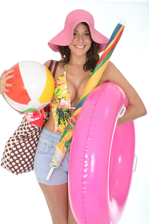 Young Woman Wearing a Swim Suit on Holiday Carrying Beach Items. A DSLR royalty free image, of attractive happy excited young woman, holding a large pink rubber royalty free stock image