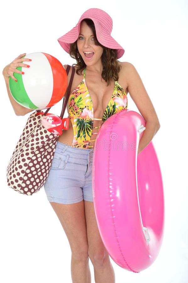 Young Woman Wearing a Swim Suit on Holiday Carrying a Beach Items. A DSLR royalty free image, of thrilled happy excited happy young woman on vacation or holidays royalty free stock photo