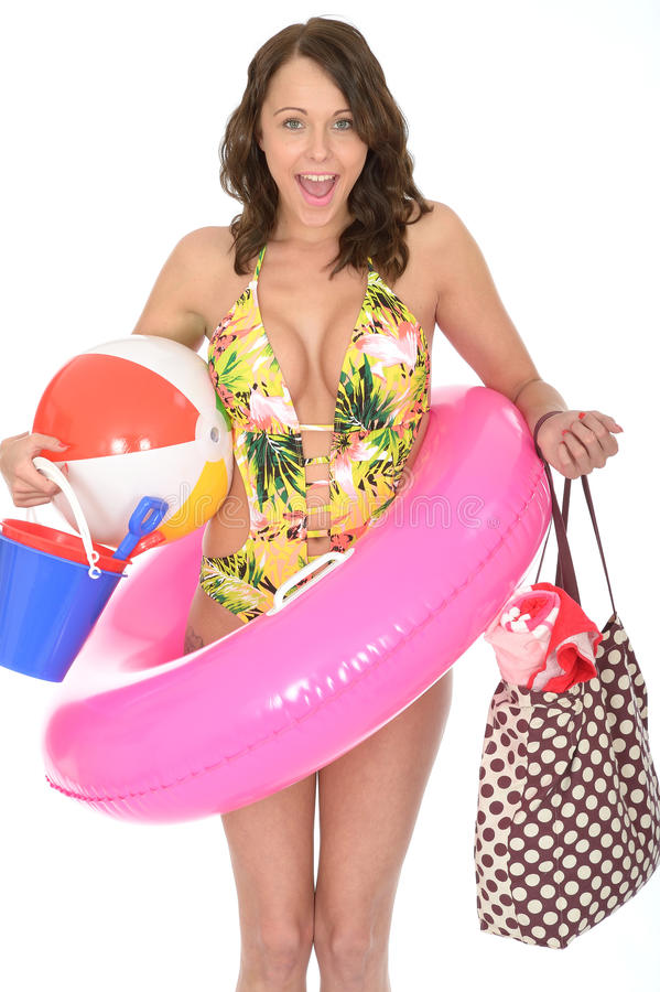 Young Woman Wearing a Swim Suit on Holiday Carrying a Bucket and Spade. A DSLR royalty free image, of very over excited happy young woman ready for her vacation stock images