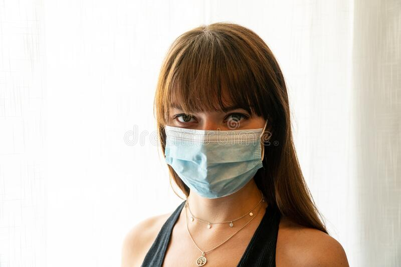 Young woman wearing teal surgical face mask royalty free stock image